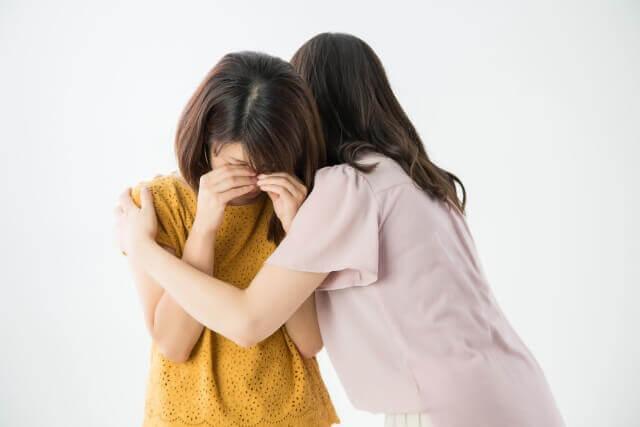 泣く友達をなぐさめる女性