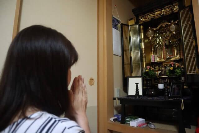 仏壇に手を合わせる女性