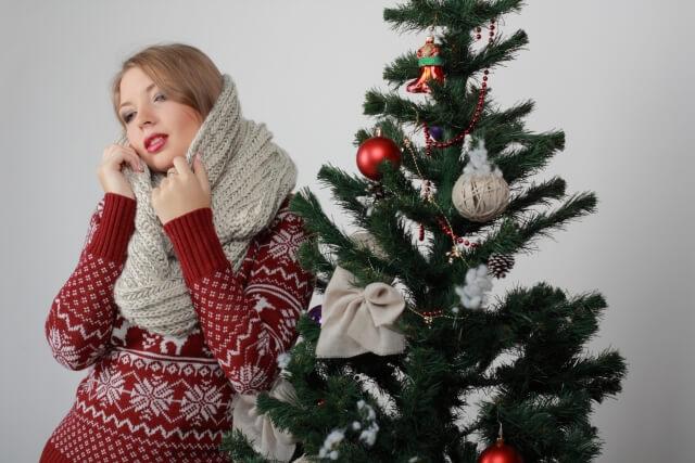 クリスマスツリーとスヌードをつけた女性