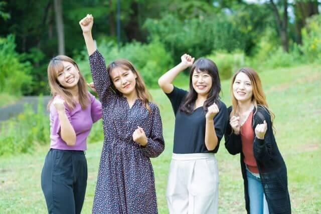ガッツポーズをする4人の女性