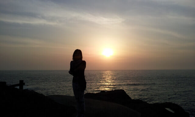 夕日を背にする女性