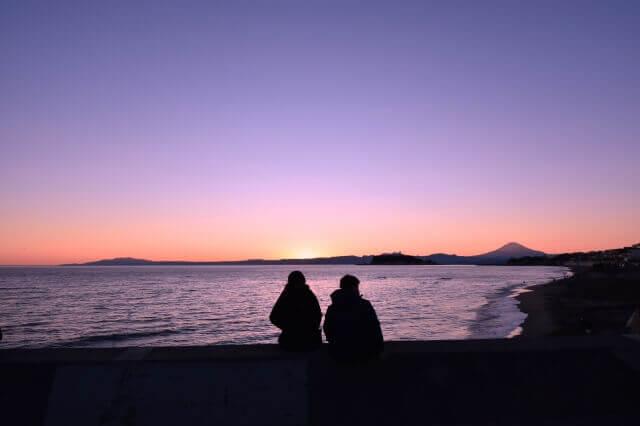 黄昏時の海辺にいる2人